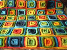 Free knitting pattern squares on a roll afghan blanket - Stocking stitch rolls add another dimension to these simple squares knitted in the round giving an exciting tactile fabric that is thick and warm. Any yarn and needles can be used.