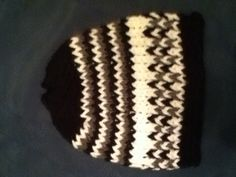 Easy loom knit hat! 1. E wrap and knit five rows in black. Cut. 2. Tie on white knit one row cut 3. Tie on grey knit one row cut 4. Tie one black knit one row cut 5. Repeat steps 2-4 two more times. 6. Knit 3 rows of white but do not cut end! 7. Alternate white & black pegs. Knit one row. 8. Alternate white & grey pegs knit one row. 9. Repeat steps 7-8. 10. Knit one row of white. 11. Knit four rows of black and knit off. Finish the bottom and sew the top together. There's your hat!
