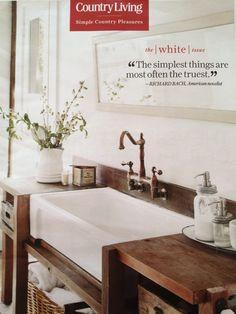 farm sink in a simple wood vanity. wall mount faucet