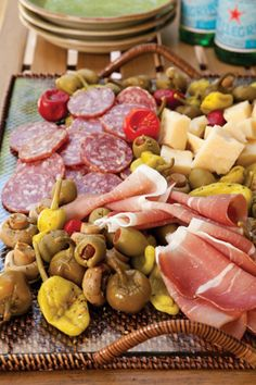 On a serving tray, arrange cubed Parmesan cheese, pepperoncini, cherry peppers, olives, jarred marinated mushrooms, prosciutto, and Italian dry sausage, such as sopressata.