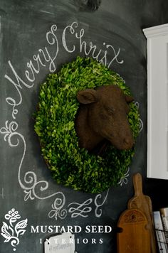 Miss Mustard Seed decorates her kitchen with a preserved boxwood wreath and cow head.