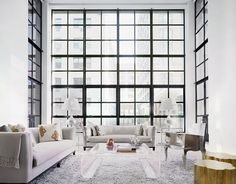 modern living room with gray sofas, an acrylic coffee table and silver arm chair