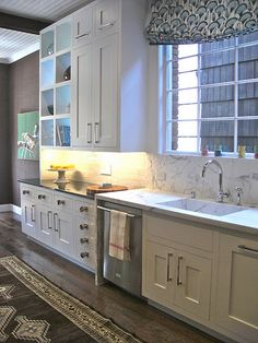 marble backsplash with dark countertops, white painted wood ceiling