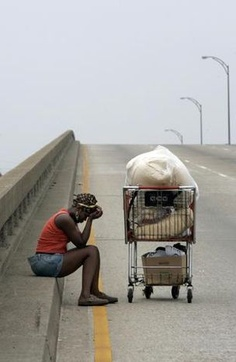 """""""Kimi Seymour, 27, of New Orleans, takes a break along Interstate 10 as she walked along the highway on Sept. 1, 2005. Seymour was displaced from her New Orleans home by Hurricane Katrina. This photo was included in the winning entry of the 2006 Pulitzer Prize for Breaking News Photography. Photo: Irwin Thompson"""""""