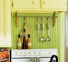 Screw cup hooks in the bottom of a wall cabinet and use fabric strips to suspend the curtain rod from the hooks.  Bend the forks in half using needle-nose pliers.  Use the pliers to curl the tines, leaving one longer to make a hook for hanging the utensils