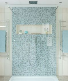 Time for ReflectionWhen you think of a rejuvenating bath, blue immediately comes to mind. This mosaic tiled shower feels open, refreshing, and cool. Accent pieces (rainfall showerhead, hanging towel racks) in shiny nickel are sleek and modern choices.