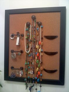 homemade jewelry holder made from a cork board and cabinet handles..The knobs are for necklaces and bracelets, the handles are for dangley or hoop earrings, and the cup-like handles are for rings and studs.