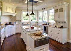 Kitchen with coffered ceiling, ivory kitchen cabinets painted Duron Shell White, kitchen island with drop down cabinet, granite countertops, subway tiles backsplash, sink in kitchen island and oil rubbed bronze industrial pendants.
