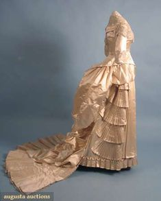 "BEADED SILK WEDDING GOWN, 1870s  Cream silk satin bodice & trained bustle skirt, white crystal beading on bodice & CF skirt panel, self-fabric pleated fans on skirt sides, fan shape train, B 31"", W 24"", Skirt L 34""-66"", (beaded trim on bodice torn, minor bead damage on skirt) good."