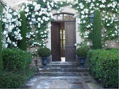 White garden, double doors, boxwood in urns