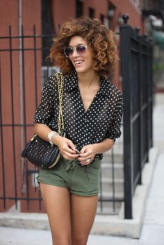 Green shorts with polka dot blouse. Love her hair and purse as well.