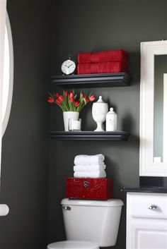shelving above toilet for towels, cute flowers in a vase, apothecary jars holding cotton swabs, etc.