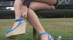Daniella outdoors in blue wedge heels, tan pantyhose tights and hot pants adjusting her ankle straps.