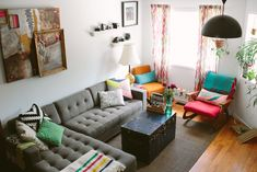 so many things I like in a living room - clean white walls, plants, big grey couch, large art, bright color pops