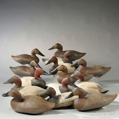"""Sold for: $2,214  Fourteen Canvasback Duck Decoys, America, early 20th century, seven drakes and seven hens, most with painted eyes, all with lead weights, one drake with glass tack eyes and scalloped edge to front dark feathers is marked """"M"""" on underside, approx. lg. 16 1/2 in.  Estimate $800-1,200"""