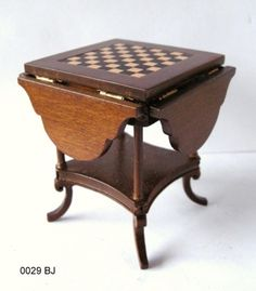 Chess Table  $70.75    Drop Leaf Chess Table with a checker board insert in the centre of the table top.    Measures 2 5/8 inch high x 3 7/8 inch square when all sides are extended. The table comes in a walnut finish.