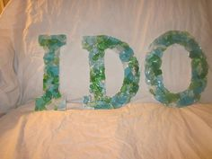 You can easily DIY cute expressions like 'I do' or 'Love' by sticking sea glass to plywood letters. Non-beachy sea glass wedding decor inspiration.