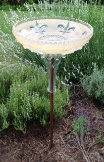 Vintage glass light shade repurposed into a bird bath.
