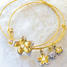 These are gorgeous! Golden Flower Charm Bracelets are probably my new favorite accessories. I know a few little girls who would love these, too!| AllFreeJewelryMaking.com