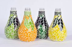 Orangina bottles each covered in over 300 pieces of hand cut stained glass mosaic. This is a one of a kind collection. This collection makes a great gift, and looks great used as decoration, or vases.