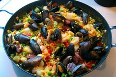 Paella is a classic Spanish rice dish traditionally made by men. Using a large, flat pan, they cooked it over a fire of orangewood and/or vine cuttings that would give off an aroma that infused the dish with flavor. This recipe is a much easier alternative to the classic technique, yet still produces a dish that is wonderful to present at the table.