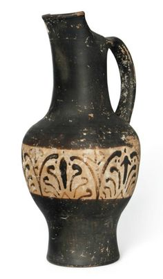 AN ETRUSCAN BLACK-FIGURED BEAK-SPOUTED OINOCHOE   CIRCA 500 B.C.   With a frieze of palmettes on the body   7 5/8 in. (19.3 cm.) high