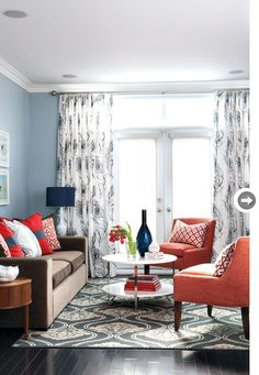 dark brown couch with grey blue wall and navy accents. coral and navy living room.