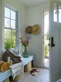 Beach house entry.  Tile floors, painted paneling, aqua bench.