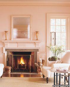 Pale pink walls create a soft, feminine-feeling living room.