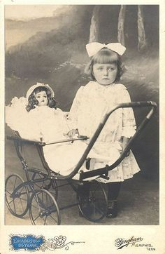 Girl with her doll in a stroller