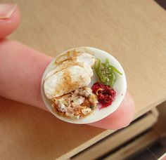 A miniaturized version of the typical Thanksgiving meal served at home (turkey slices served alongside stuffing, cranberry sauce and green beans). Handcrafted entirely from polymer clay to one inch (dollhouse) scale, the meal is secured to a ceramic plate measuring 13/16ths of an inch in diameter.