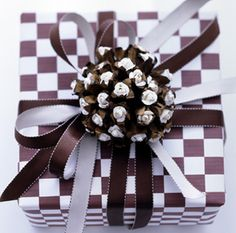 Pinecone with a dallop of white paint on the ends; garnishes brown and white checker board gift wrap.