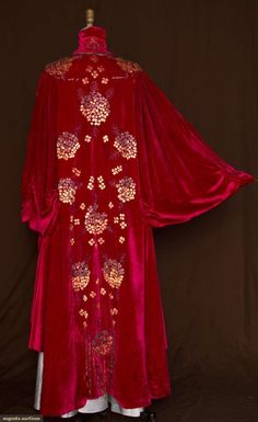 BEADED VELVET OPERA COAT, c. 1910    Raspberry silk velvet covered in hydrangeas with bat-wing sleeves, high neck and uneven length
