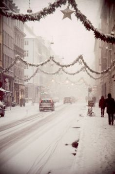 """I remember decorations like this """"downtown"""" when I was little. (That is where everyone shopped because there were no malls.)  I love the hanging street lamps above the garland.   In the misty snow this quaint street just shouts Merry Christmas to me!"""