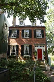 brick with red door/black shutters