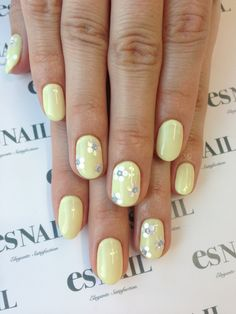 Yellow nails with daisy accents.