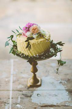 pale yellow lemon wedding cake with flower cake topper - the soft iced cake looks amazing on the brass cakestand #weddingcake