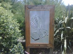 Garden Art of a NZ fantail bird made of sheet metal framed in treated pin. Here to greet all the real fantails that flit close by when we're mucking around in the garden.