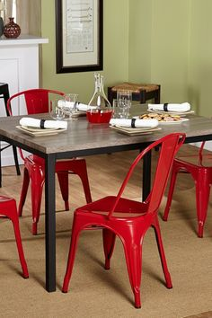 Grey reclaimed dining table with red metal chairs.