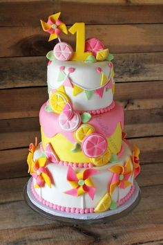Pinwheels & Pink Lemonade Twins 1st Birthday Cake - Designed for twins girls 1st birthday. It's 3 tiers of vanilla cake filled with vanilla buttercream and covered with homemade marshmallow fondant. The decorations are mostly modeling chocolate with some fondant.