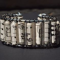 Hand crafted guitar string cuff bracelet with sheet music paper beads