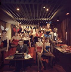 Slim Aarons;   Working at his typewriter surrounded by 'bunny girls', publisher Hugh M Hefner at the Playboy Key Club in Chicago. He founded adult magazines, Playboy, VIp and Oui.