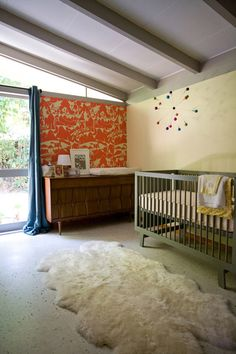 I like the sheep skin, the Mid-century dresser, the crib  the idea of having light walls with a wallpapered accent wall. Nursery baby