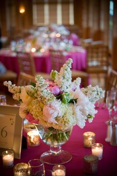 White hydrangea, peony, tulip and lilac centerpieces on hot pink linens.