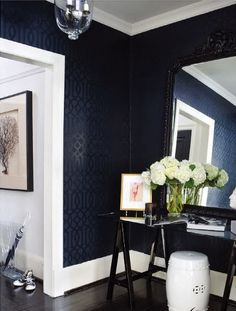 Chic foyer with Kelly Wearstler Imperial Trellis Wallpaper, white garden stool, glossy glasstop black table, ornate mirror and clear acrylic umbrella stand.