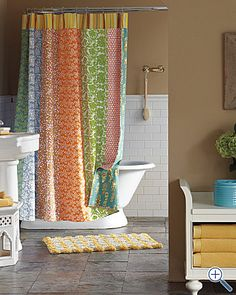 guest bathroom idea: love the tub and tiled wall. cute colorful shower curtain too