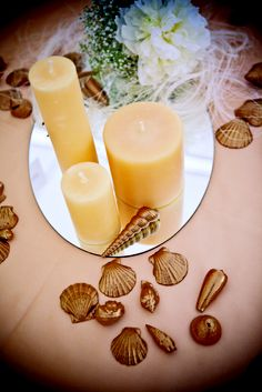 A romantic centerpiece of candles sprinkled with gilded seashells.