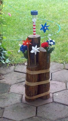 Diy solar walk light made from logs, rope, solar light, pinwheels, and flowers