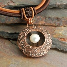 Copper Lentil with floating pearl. This peice is featured in the summer 2010 special edition Metal Clay Jewerly magazine.