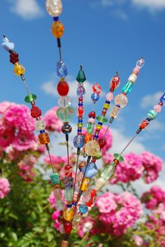 DIY: Beaded Blossom Suncatcher.  Make multiples to stick in the ground near evergreens/herbs/etc.  Be sure to use glass beads, since plastic is prone to fading from extended sun exposure!  I'm going to put mine into my bedroom window boxes because I can't see the garden from my bed as the window is too high. I'm so glad I found this on Kathy's superb board.